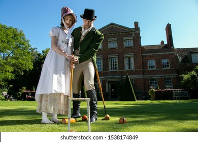 Handsome man and beautiful woman dressed in vintage clothing on lawn in front of stately home, playing croquet with blue sky
