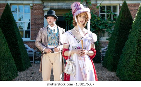 Handsome man and beautiful woman dressed in vintage clothing, standing in front of stately brick home