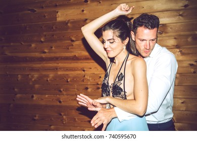 Handsome man and beautiful woman in fancy dress dancing together at private party.