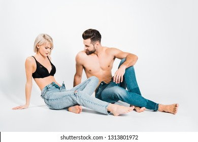 handsome man and beautiful woman posing in underwear and jeans on grey