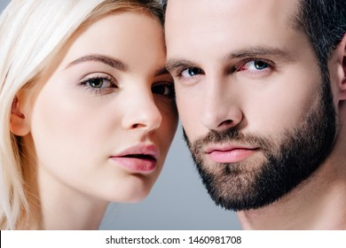 handsome man and beautiful young woman looking at camera isolated on grey