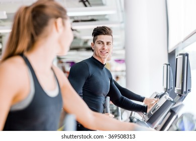 Handsome man and beautiful young woman using a stepper in a gym and having a conversation