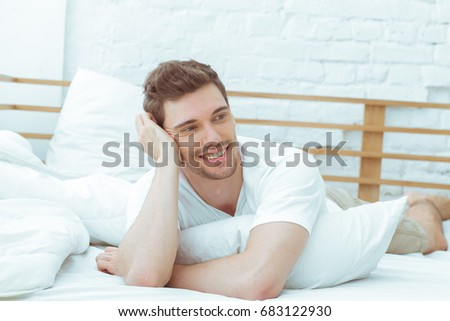 Handsome guy relaxing on a bed