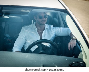 Handsome Man Behind the Wheel Driving a Car, wearing white shirt, hand on wheel