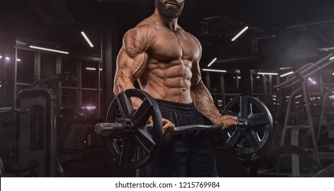 handsome man with big muscles trains in the gym, exercises