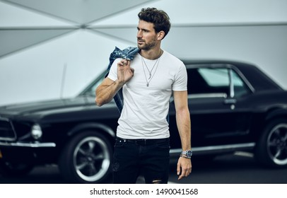 Schöner Mann mit schwarzem Oldtimer trägt schlaue, lockere Kleidung