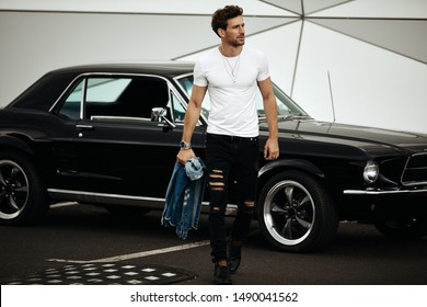 Handsome man with black old car waliking on the parking