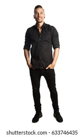 Handsome man in black shirt and black jeans, standing against a white background feeling great and comfortable with a smile.
