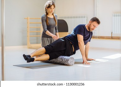 Handsome man in black sportswear using a foam roller on the ground, female rehabilitation specialist instructor help him in modern pilates studio. Rehabilitation restoring after injury concept.