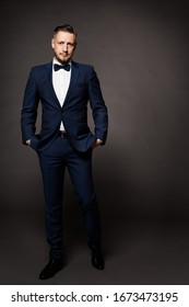 Handsome Man in Black Suit, Elegant Fashion Model Studio Portrait in Tuxedo, Hands in Pockets