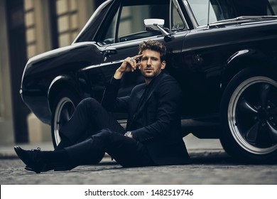 Handsome man in black suit is sitting on the floor near by his classic car