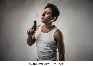 handsome man blowing on the gun