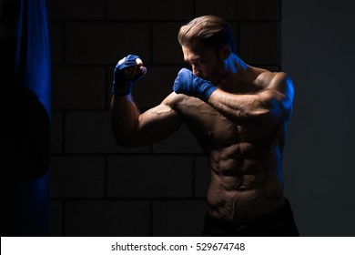 Handsome Man In Blue Boxing Gloves - Boxing In Gym - The Concept Of A Healthy Lifestyle - The Idea For The Film About Boxing