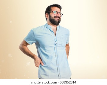 Handsome man with blue glasses with back pain on ocher background