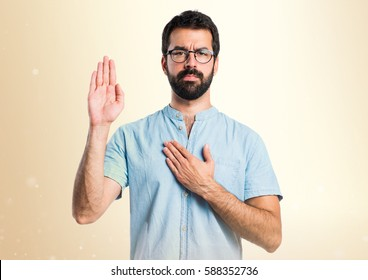 Handsome man with blue glasses making an oath on ocher background