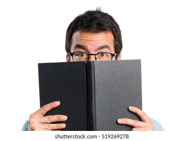 Handsome man with blue glasses reading book