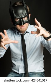 handsome man in blue shirt and batman mask angry at black background