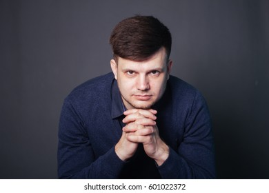 A handsome, handsome man in a blue shirt. Fashionable photo in the studio on a gray monophonic background.