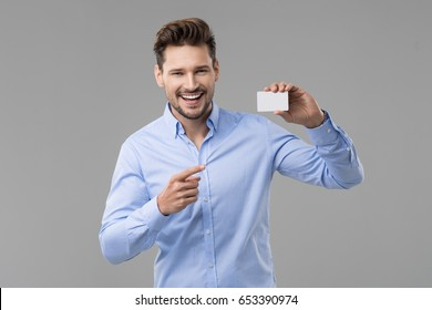 Handsome man in blue shirt  with white card