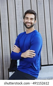 Handsome man in blue smiling at camera