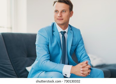 The handsome man in a blue suit. A portrait of the young groom in the interior. Portrait of the successful young businessman