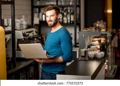 Handsome man in blue sweater working with laptop at the bar of the modern cafe interior