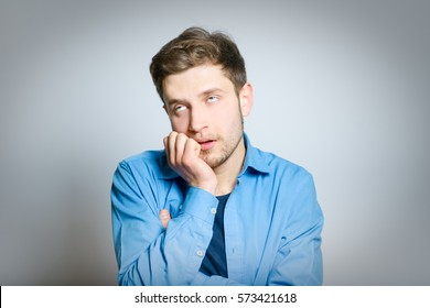 Handsome man is bored, isolated on a gray background