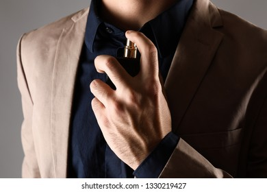 Handsome man with bottle of perfume on grey background, closeup
