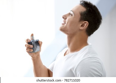 Handsome man with bottle of perfume on light background