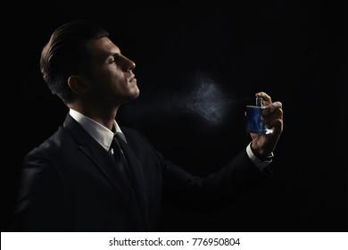 Handsome man with bottle spraying perfume on dark background
