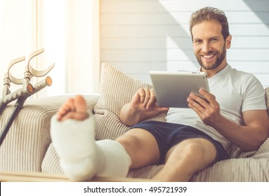 Handsome man with broken leg is using a digital tablet, looking at camera and smiling while sitting on couch at home