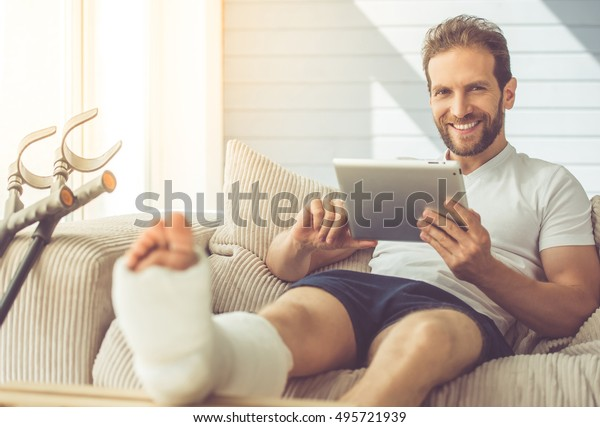 Ein ansehnlicher Mann mit gebrochenem Bein benutzt eine digitale Tablette, sieht sich die Kamera an und lächelt, während er zu Hause auf der Couch sitzt