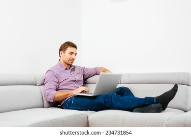 Handsome man browsing the web and sitting on a couch