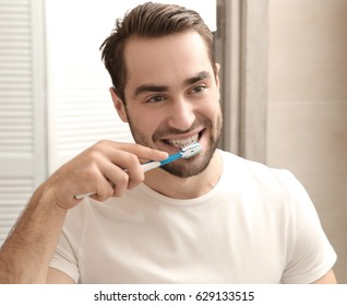 Handsome man brushing teeth in bathroom
