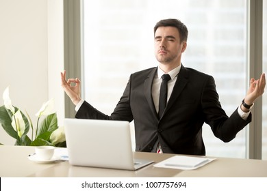 Handsome man in business suit meditating with closed eyes at work desk with laptop. Successful businessman practicing eastern spiritual practices at office workplace for relaxing and stress relief