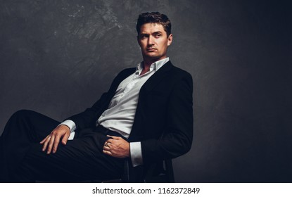 Handsome man in a business suit sits on a chair and looks away, portrait