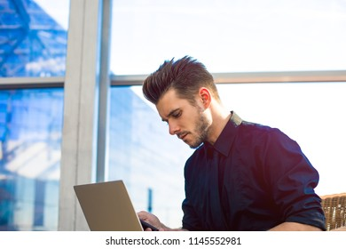 Handsome man business worker reading notification on mobile phone and using laptop computer, sitting in skyscraper building. Bearded male financier in formal wear sending sms via smartphone gadget