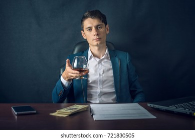 Handsome Man Businessman in suit sitting in chair. Boss drink alcohol in the glass and enjoys the success. The concept of a successful business