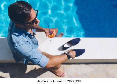 Handsome man by the pool, drinking cocktail