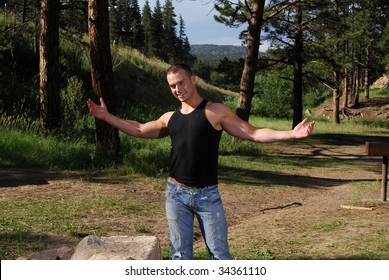 A handsome man in a campground holding his arms out wide