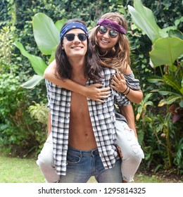 handsome man carrying beautiful girl on back , woman hugging guy. Hippie and gypsy style. they are wearing sunglasses and bandanas