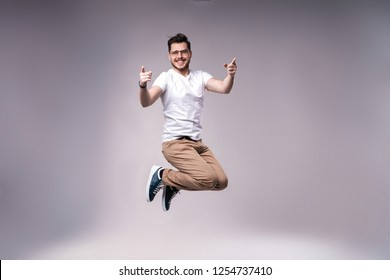 handsome man casual dressed celebrating and jumping on gray background.