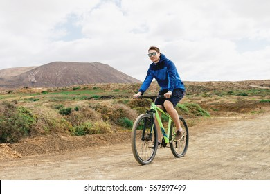 handsome man  in casual outfit ride a mountain bike on Canaries island