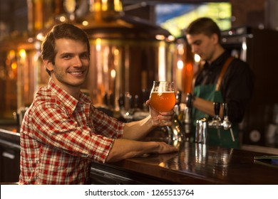 Handsome man in checked shirt sitting at bar counter and holding glass of beer. Client of brewery looking at camera, smiling and posing. Barmen working and bronzed kettles behind.