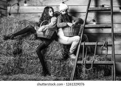 Handsome man chef cook or baker with beard and moustache in hat toque and cute girl cookee teenager in apron sit on straw bales with baskets on rustic background.