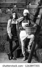 Handsome man chef cook or baker with beard and moustache in hat toque with cute girl  in apron stand at wooden ladder with basket on rustic background.