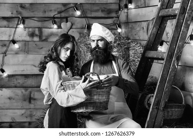 Handsome man chef cook or baker with beard and moustache in hat toque with cute girl cookee teenager in apron stand at wooden ladder with basket on rustic background.