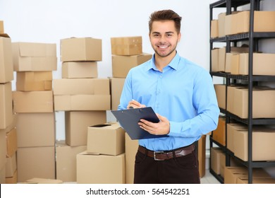 Handsome man with clipboard in logistics company warehouse