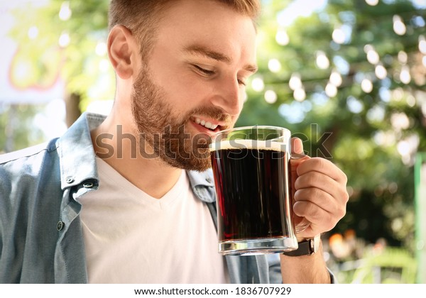 Handsome man with cold kvass outdoors, closeup. Traditional Russian summer drink