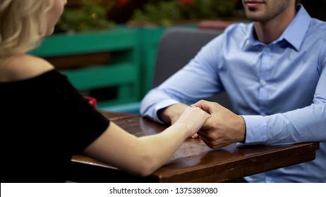 Handsome man confessing his love to beautiful girlfriend, holding her hand